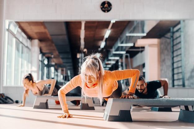 Gruppe von sportlichen leuten, die liegestütze auf steppern im fitnessstudio machen. selektiver fokus auf blonde frau, im hintergrundspiegel.