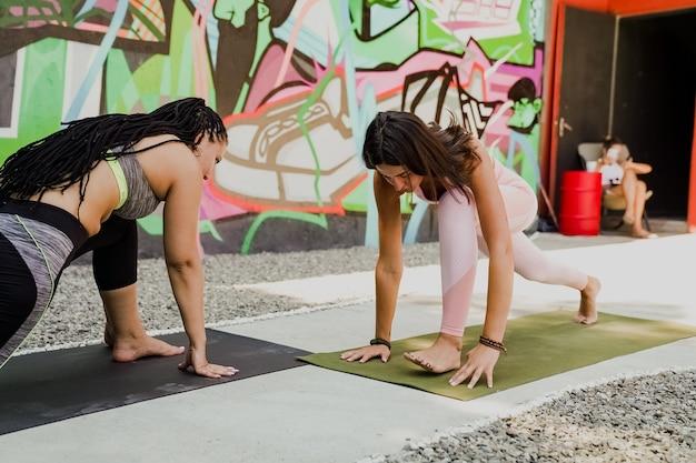 Gruppe von sportlichen leuten und yogalehrer, die yoga im freien machen