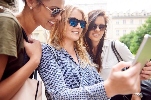 Gruppe von stilvollen frauen, die in der stadt genießen und ein digitales tablet verwenden