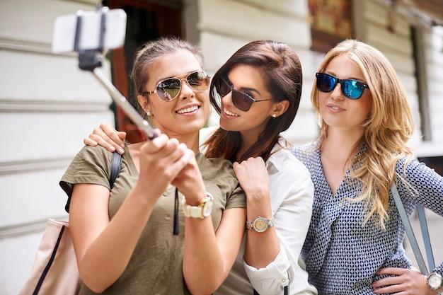 Gruppe von stilvollen frauen, die in der stadt genießen und ein foto machen