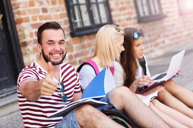 Gruppe von studenten, die auf dem campus sitzen