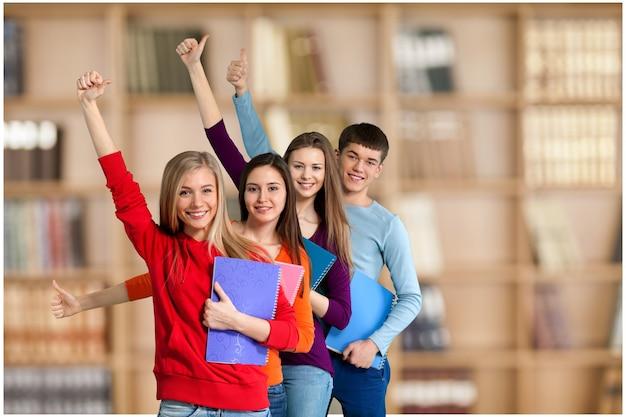 Gruppe von studenten, die daumen nach oben auf den hintergrund gestikulieren