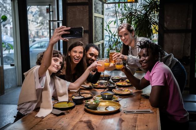 Gruppe von studenten, die mit der telefonkamera ein selbstporträt machen