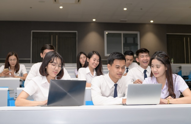 Gruppe von studenten, die mit laptop im klassenzimmer arbeiten