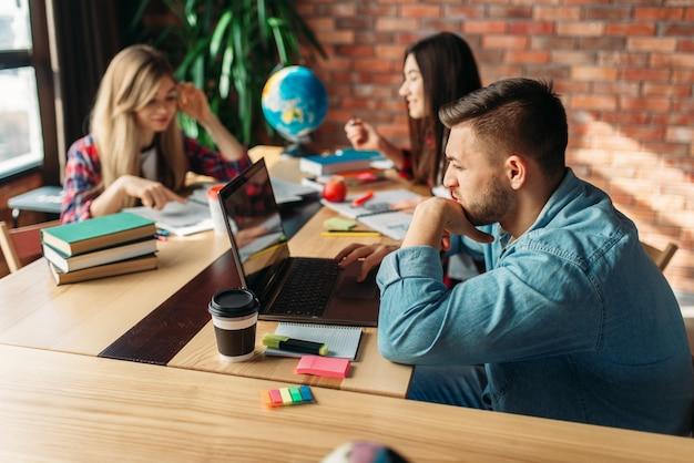 Gruppe von studenten, die zusammen am tisch lernen