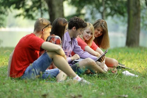 Gruppe von studenten mit einem laptop, der auf dem rasen im park sitzt.