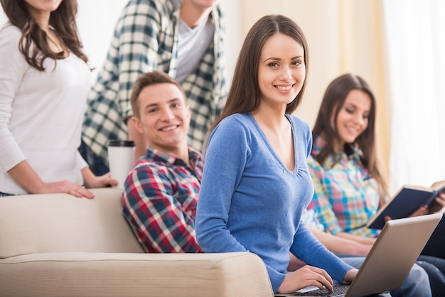 Gruppe von studenten sitzen auf dem sofa mit laptop und buch.