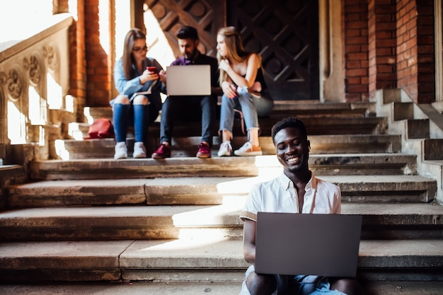 Gruppe von studenten studiert in der nähe der universität in der nähe des campus mit laptops