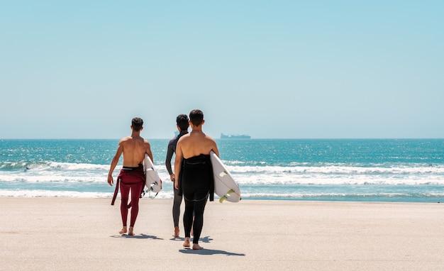 Gruppe von surffreunden, die mit ihren brettern ans meer gehen, um zu surfen