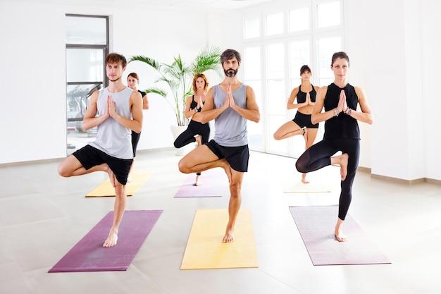 Gruppe von tausendjährigen menschen, die in tree pose oder vrikshasana stehen und yoga in geräumigem studio praktizieren