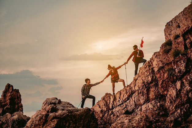 Gruppe von teamleuten, die bei der arbeit am gipfelbergsteigen helfen, teamwork-reisetrekking-gewinner