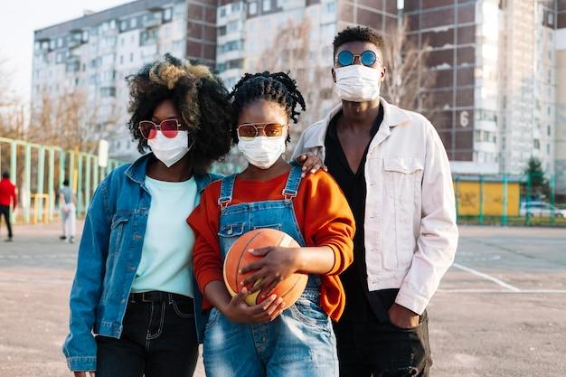 Gruppe von teenagern, die mit medizinischen masken aufwerfen