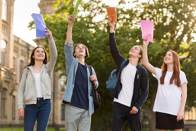 Gruppe von teenagern glücklich, wieder an der universität zu sein