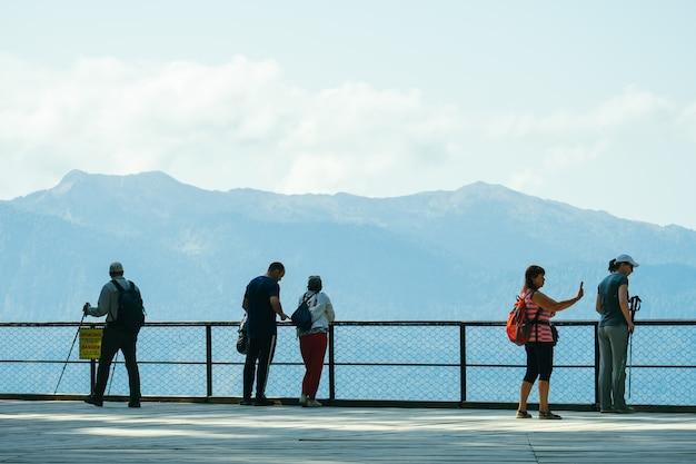 Gruppe von touristen, die auf aussichtsplattform in den bergen zurück zur kamera stehen