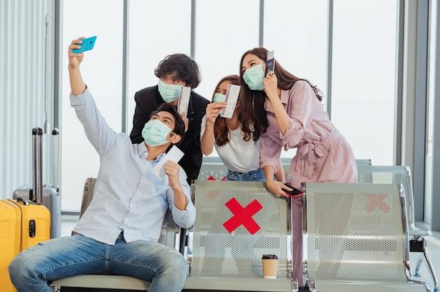 Gruppe von touristen, die vor ihrem flug ein selfie am flughafen machen