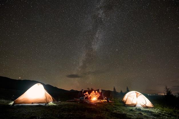 Gruppe von touristen mit gitarre durch brennendes lagerfeuer unter dunklem sternenhimmel mit milchstraßenkonstellation.