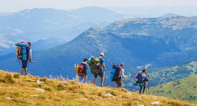 Gruppe von touristen mit outfit auf blauen bergen
