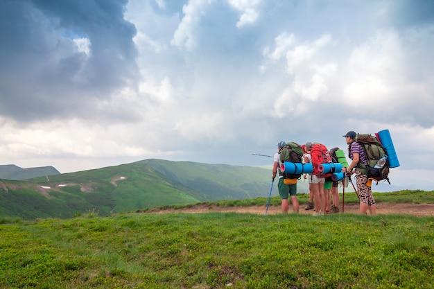 Gruppe von touristenwanderern, die in den bergen stehen, die ihr ziel betrachten