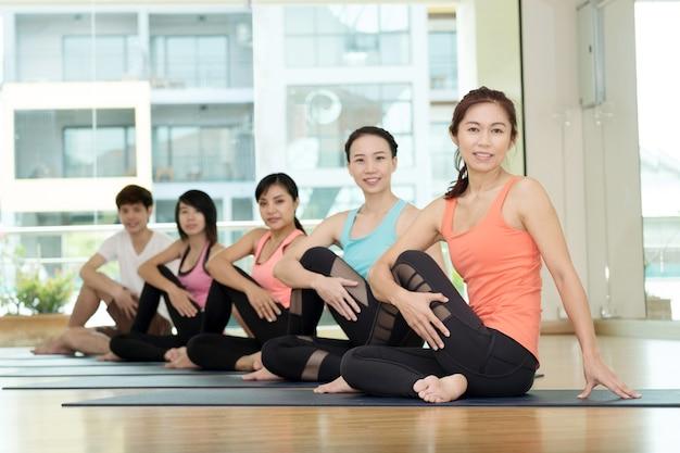 Gruppe von übenden yoga der asiatischen frauen und des mannes, eignung, die flexibilitätshaltung, ausarbeitend, studiohintergrund ausdehnt