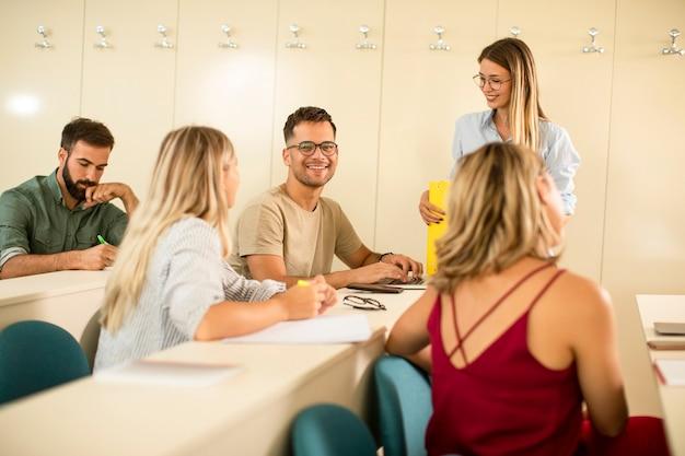 Gruppe von universitätsstudenten im klassenzimmer mit junger dozentin
