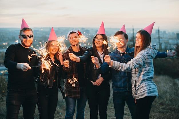 Gruppe von verblüfften jungen leuten in party- und weihnachtshüten lächelnd und brennende wunderkerzen