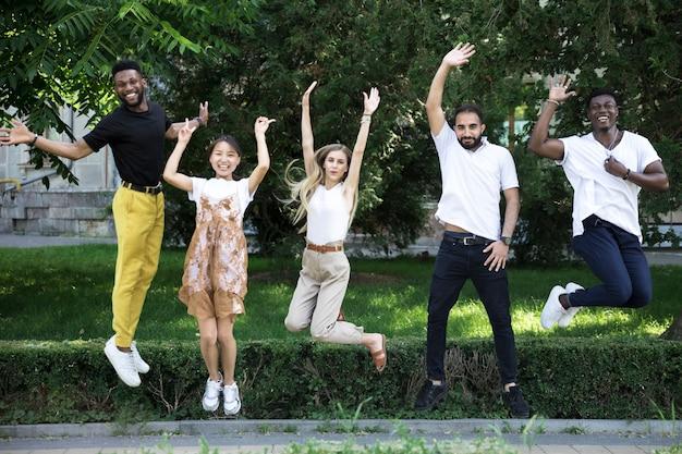 Gruppe von verschiedenen freunden springen