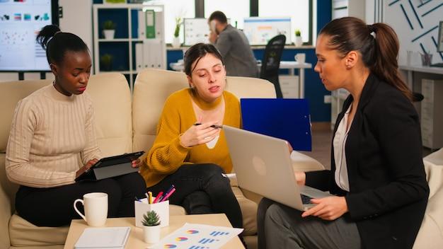 Gruppe von verschiedenen startup-unternehmenskollegen, die sich am professionellen arbeitsplatz treffen, ideen über das management von finanzstrategien austauschen und teilen. glückliche gemischtrassige geschäftsleute, die spaß an der arbeit haben