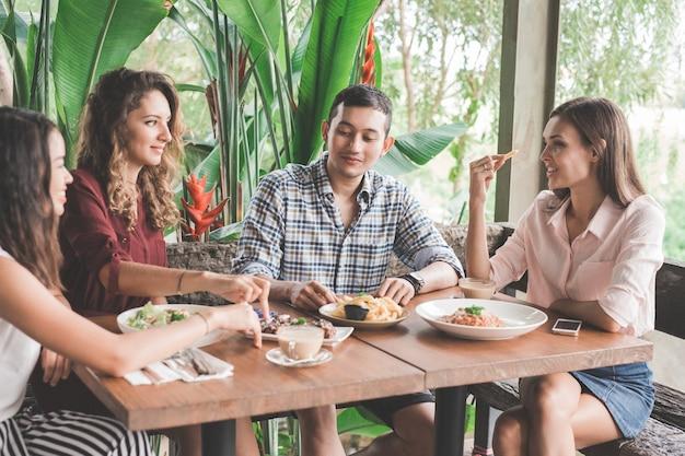 Gruppe von vier besten freunden, die zusammen in einem café zu mittag essen