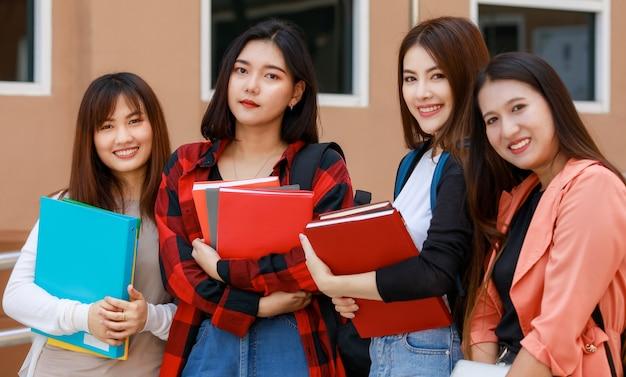 Gruppe von vier college-studenten, die bücher zusammenhalten und mit lächeln in die kamera blicken, stehen vor dem schulgebäude. lernen und freundschaft des konzepts der engen freunde von teenagern.