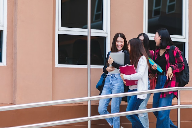 Gruppe von vier college-studenten, die vor dem schulgebäude mit intimität zusammengehen und sprechen. lernen und freundschaft des teenagerkonzepts.