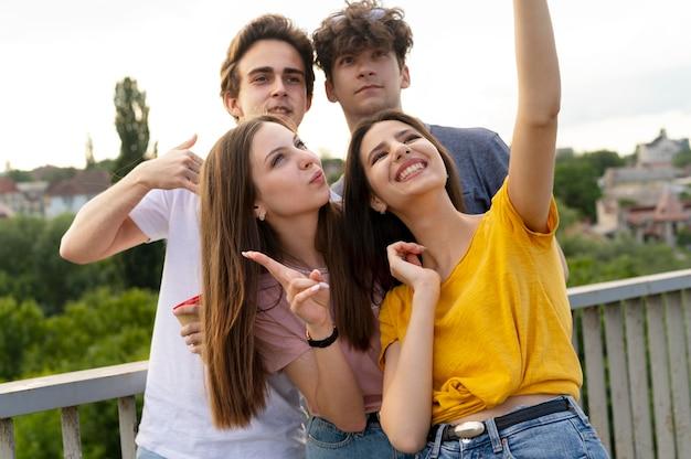 Gruppe von vier freunden, die zeit zusammen im freien verbringen und selfies machen