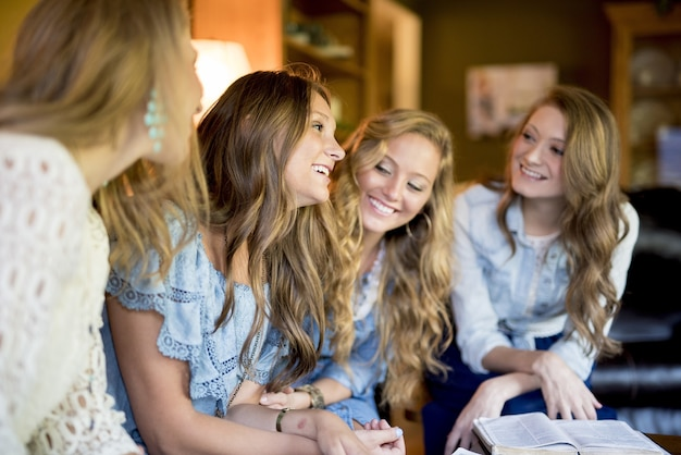 Gruppe von vier freundinnen, die beim lesen im haus lachen