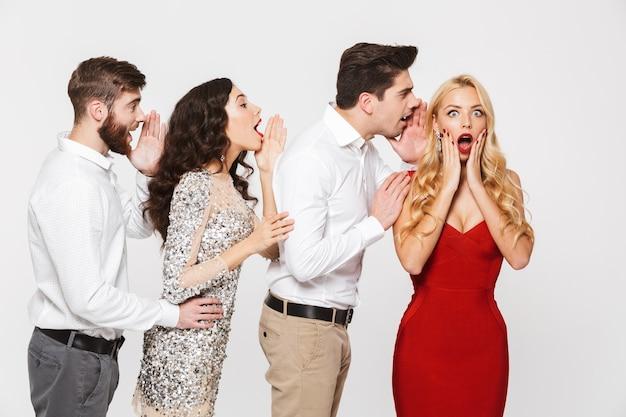 Gruppe von vier fröhlichen menschen, die klug gekleidet sind und sich gegenseitig geheimnisse erzählen, isoliert über weiß