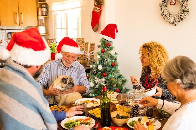 Gruppe von vier personen, die den weihnachtstag und das gemeinsame mittagessen zu hause mit einem mops genießen, der auf einem alten mann sitzt - glückliche erwachsene und senioren, die essen und trinken