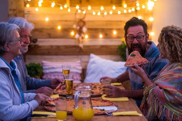 Gruppe von vier personen, die zu hause oder im restaurant mit pizza und bier zusammen essen - lustige szene einer frau, die ihrem ehemann oder freund eine pizza gibt