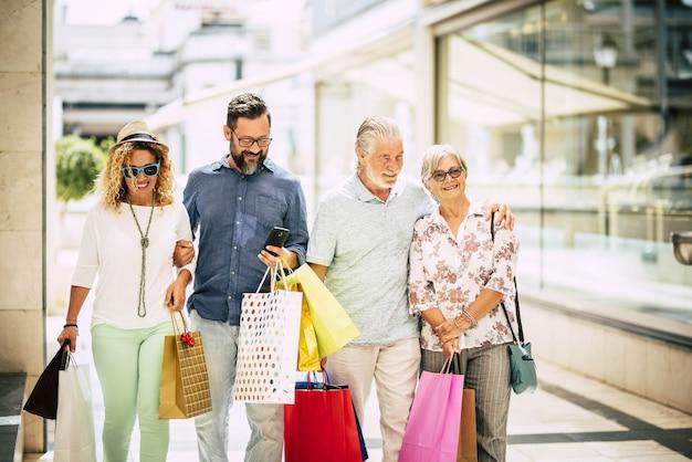 Gruppe von vier personen, die zusammen in einem einkaufszentrum mit einkaufstüten einkaufen - cyber monday und black friday
