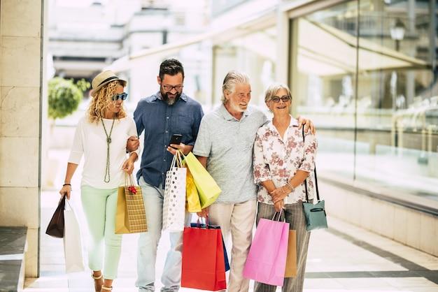 Gruppe von vier personen mit erwachsenen und senioren, die im einkaufszentrum einkaufen und einkaufen, zusammen nach geschäften suchen und geschenke oder kleidung in den einkaufstaschen in den händen tragen