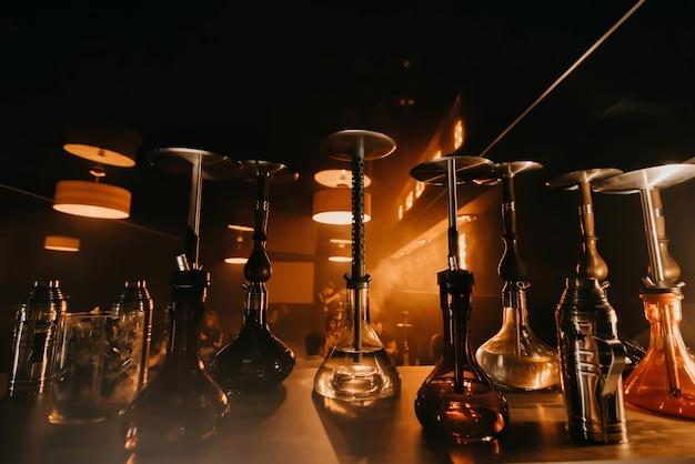 Gruppe von wasserpfeifen mit shisha-glasflaschen und metallschalen