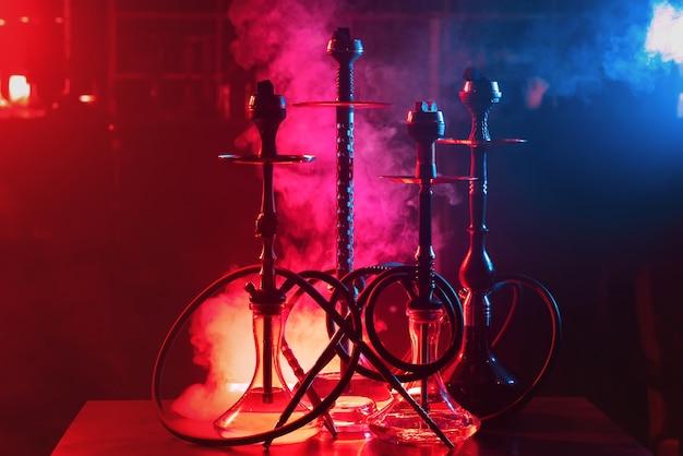 Gruppe von wasserpfeifen mit shisha-kohlen in schalen auf einem roten und blauen hintergrund mit rauch