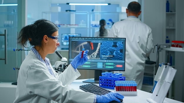 Gruppe von wissenschaftlern, die laborkittel tragen, die im labor arbeiten, während sie biochemische proben in reagenzgläsern und wissenschaftlichen instrumenten untersuchen