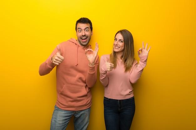Gruppe von zwei leuten auf dem gelben hintergrund, der okayzeichen zeigt
