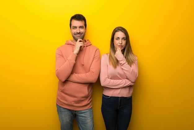 Gruppe von zwei leuten auf gelbem hintergrund lächelnd und schauen zur front