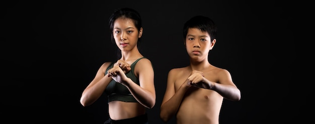 Gruppe von zwei meister black belt taekwondo karate junge mädchen, das athlet schwester bruder teenager ist zeigen traditionelle kampf posen, schwarze wand isoliert kopie raum