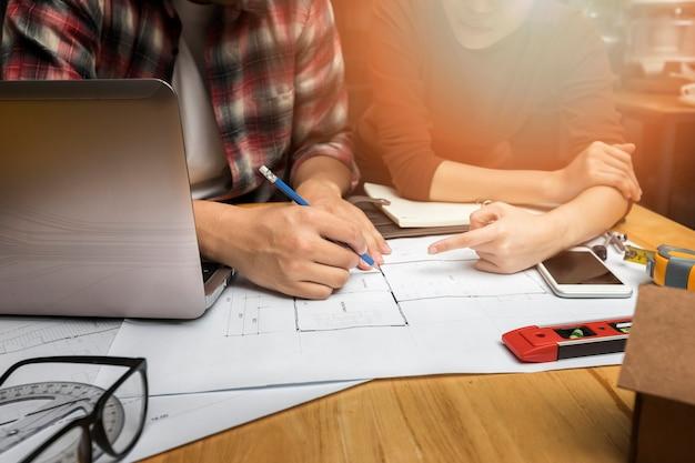 Gruppe von zwei mitarbeitern, die im büro mit blaupausen arbeiten. co-working-teamwork-konzept.