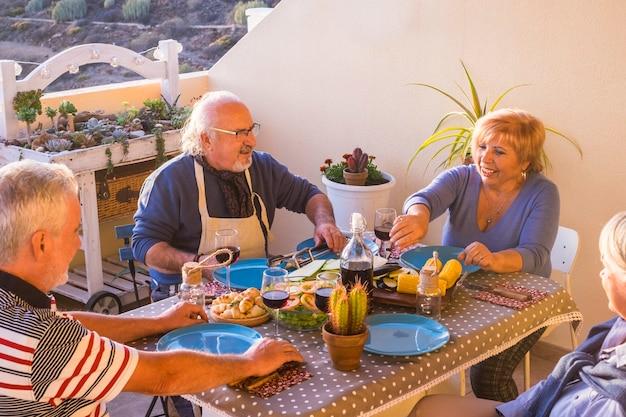 Gruppe von zwei paaren kaukasischen erwachsenen, die zu hause auf der terrasse zusammen essen und spaß haben