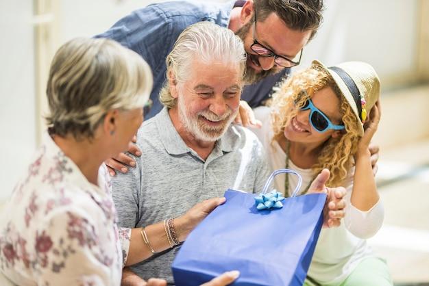 Gruppe von zwei senioren und zwei erwachsenen zusammen im einkaufszentrum - drei leute, die dem reifen mann zu seinem geburtstag oder zu weihnachten ein geschenk machen