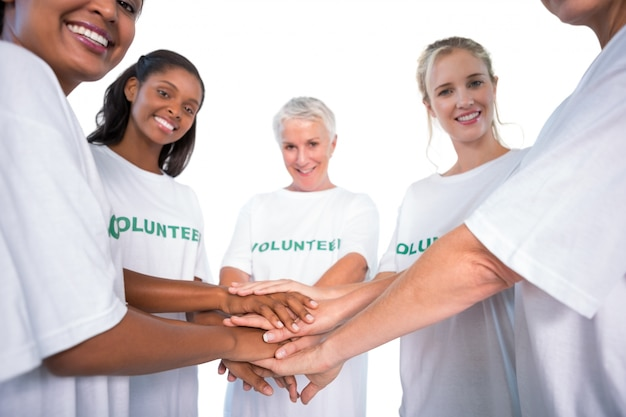 Gruppe weibliche freiwillige mit den händen, die zusammen an der kamera lächeln