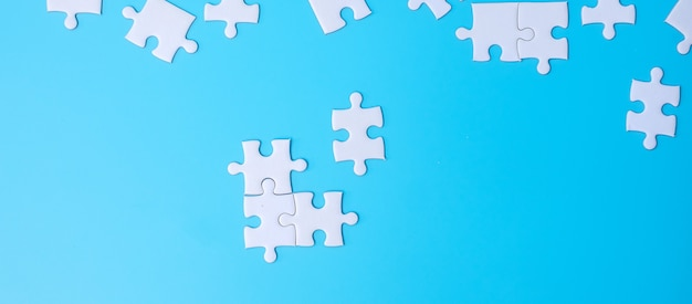 Gruppe weiße puzzleteile auf blauem hintergrund. lösungskonzept, mission, erfolg, ziele, zusammenarbeit, partnerschaft, strategie und puzzletag