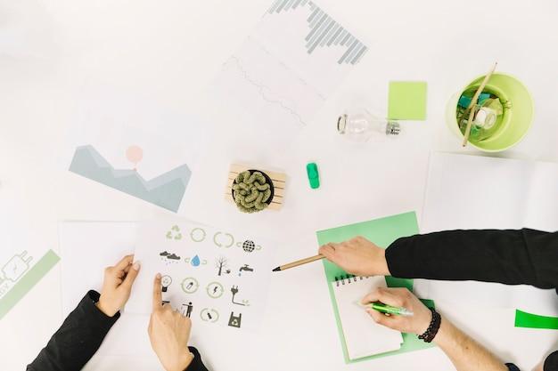 Gruppe wirtschaftler, die an papier mit energiesparenden ikonen arbeiten