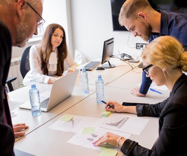 Gruppe wirtschaftler, die die unterschiedliche art des diagramms auf tabelle im büro analysieren